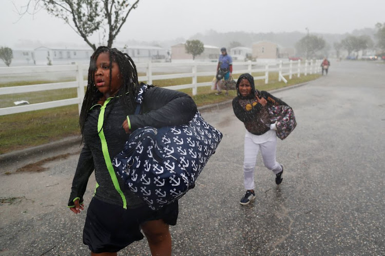 During a driving rain children evacuate from a flooding trailer community during Hurricane Florence in Lumberton, North Carolina, on September 15 2018.