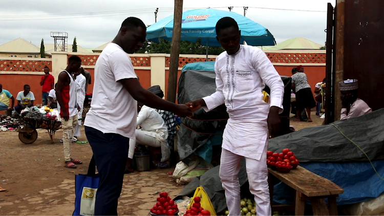 Emmanuel Peter, customer at Dutse market, Abuja exchanging cash for goods with a trader.