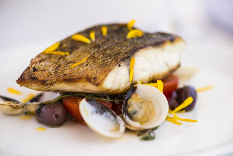 Red drum sea bass with clams, tomatoes, olives and herbs.