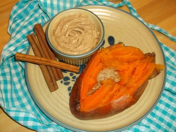 Baked Sweet Potato On A Plate With Cinnamon Honey Butter In A Ramekin.