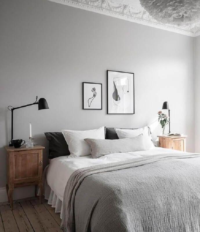 Quarto decorado com cores neutras,  piso e criados mudo amadeirado e luminárias pretas.