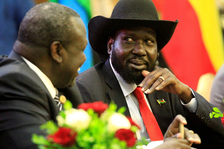 South Sudan's President Salva Kiir (R) talks to South Sudan's rebel leader Riek Machar as they sign a cease fire and power sharing agreement with in Khartoum, Sudan August 5, 2018.
