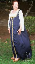 Photo: Vestido Império em linho e renda com mangas franzidas de renda branca e capa em seda azul com galões dourados bordados e botões frontais dourados de brasão. A partir de R$ 600,00.