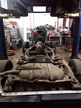 Photo: After some quick work has been done underneath the hood, it is time to reposition the lift, and pick the body right up off the chassis. It may surprise you, but other than 10 bolts, there is not much more holding the passenger compartment from the frame. As you can see on at the bottom left of the picture, the frame has suffered extensive damage to the point where the backmost bolts on the frame have ripped right through from the upper body. As the frame is one complete piece, the whole thing needs to be swapped, that means stripping it to the ground, and rebuilding it.