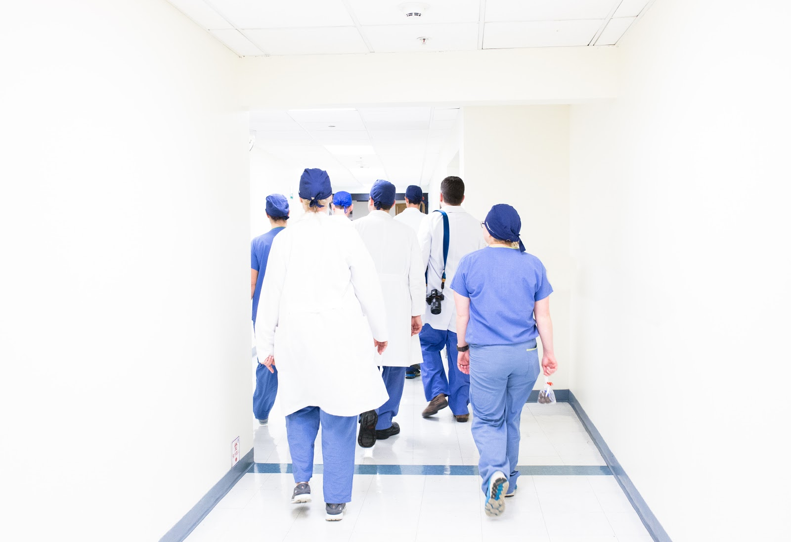 A picture of some doctors/nurses walking down a white corridor.