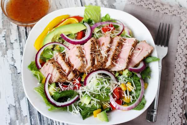 Tuna Steak Salad On A Plate With Dressing On The Side.