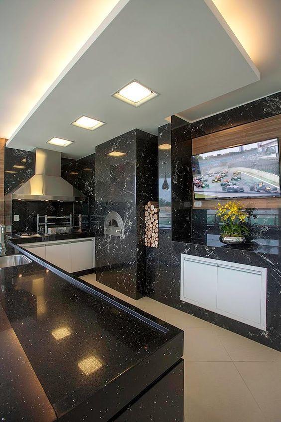 Área gourmet com paredes, churrasqueira e bancadas revestida de granito preto, coifa de inox e porcelanato em cor neutra.