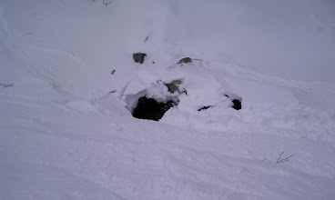 Photo: A bit hard to see in this picture, but showing ski tracks (not ours!) that went right up (over?) a collapsing hole on the approach to the Little Headwall.  (Note that prior ski tracks already sensibly led the way up on the bank to the skier's right to avoid all that.)