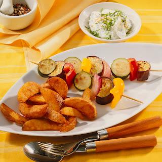 Kartoffelspalten mit Gemüsespießen und Dip