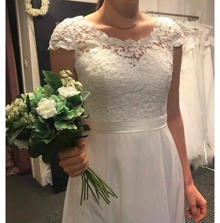 Brudklänning i grövre spets med liten ärm och chiffongkjol