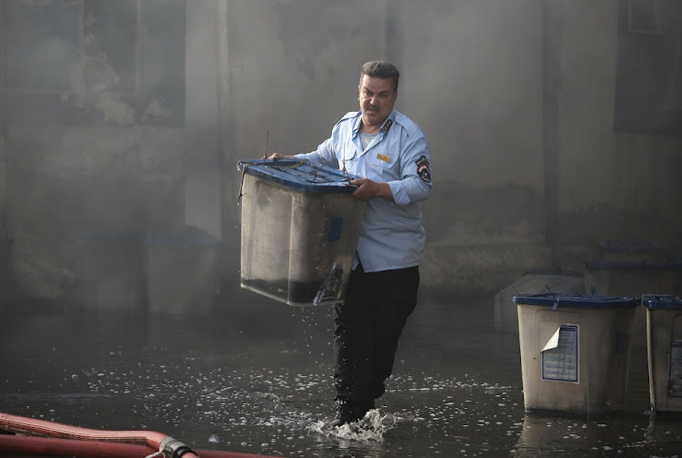 An official carries a ballot box after a fire at a storage site in Baghdad, Iraq, June 10 2018. Picture: REUTERS