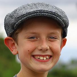 Lad with a Cap by Chrissie Barrow - Babies & Children Child Portraits ( grin, cap, teeth, portrait, boy, child, smile )