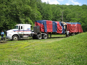Photo: Here comes the house! We unload the panels in a neighbor's field because the road to our site is too narrow and steep for a big truck.