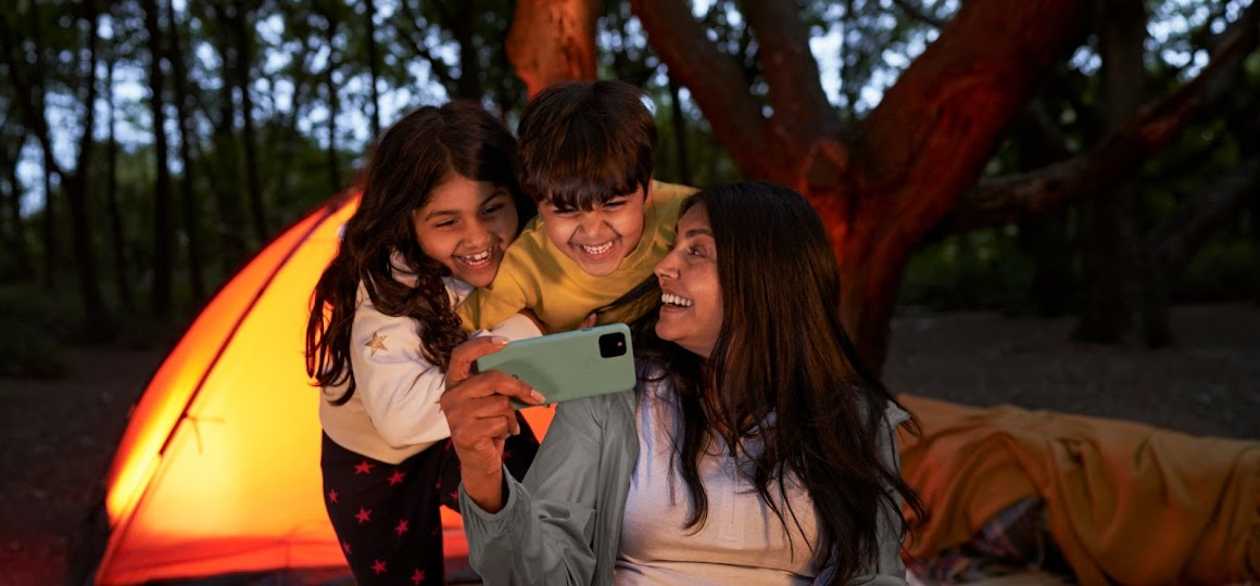Mother and her two young children sit around a campfire, sharing memories on Pixel 5 while camping.