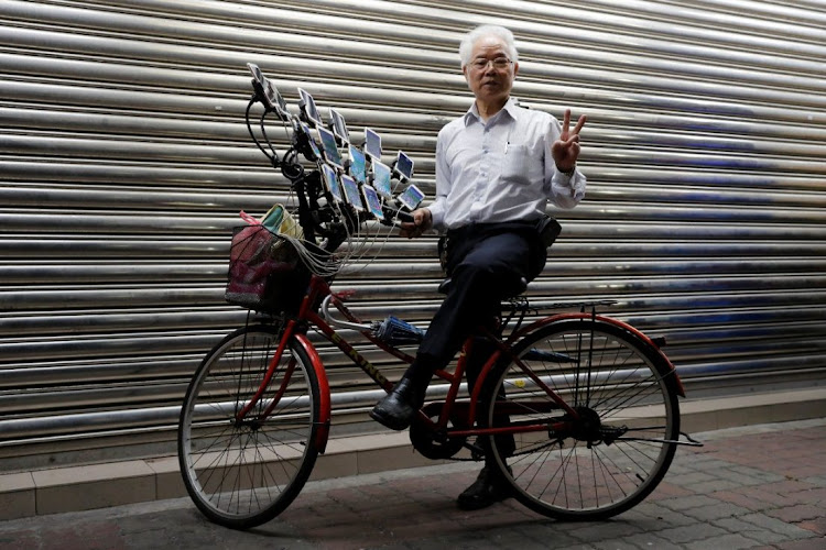Taiwanese 'Pokemon grandpa' poses with his bicycle as he plays Pokemon Go in New Taipei City.