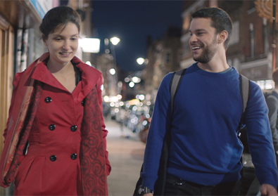Founders, Elina and Adam, are walking along a sidewalk at night.