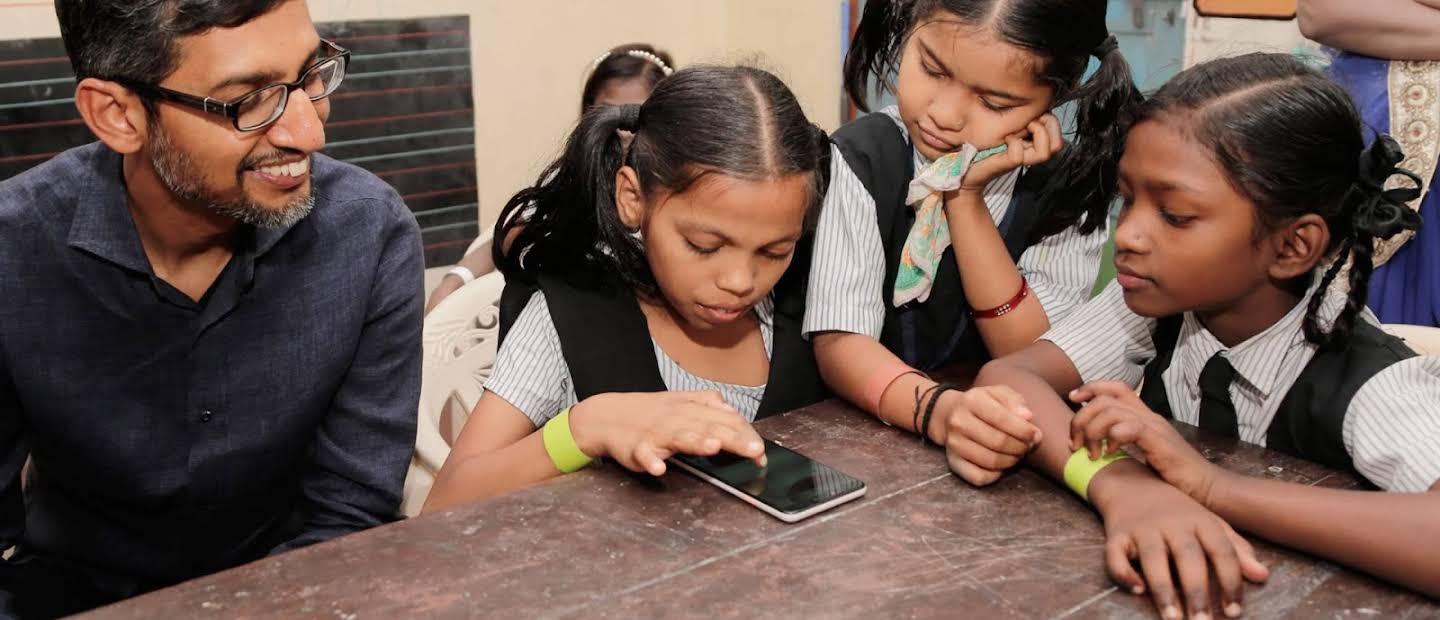 Sundar Pichai interacting with three school girls in uniform all focusing on a smartphone device