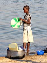 Photo: Cóbuè - a girl washing plates in the lake