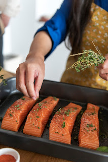 woman putting seasonings on salmon