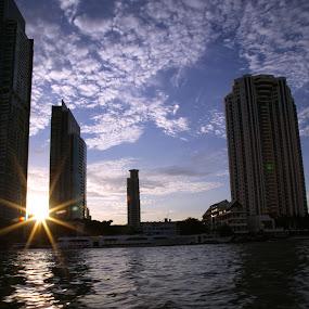 The departing sun over river by Kaniz Khan - Landscapes Waterscapes ( water, building, waves, floating sky, sun, bangkok, sky, skyscraper, sunset, wave, ripple, cloud, kaniz khan, evening, river,  )