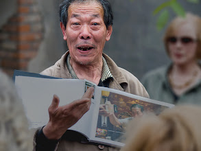 """Photo: Photoshop CC Before & After I may yet save some """"lost"""" photos.  Mr. Lee #3  This is Mr. Lee (or perhaps, Mr. Li), a retired international cricket wrangling champion. Here, he shows a group of onlookers his scrapbook of newspaper clippings and mementos. Later he regaled the group with some of his live crickets and grasshoppers. He is an enormously entertaining character.  The disappointment with the raw file I captured was that it was quite unsharp due to a bit of camera shake and probably, just missing the mark with lens focus. I have produced versions of this photo several times, coming to some reasonably acceptable compromises, since the expression on Mr. Lee's face is simply too precious to disregard the photo altogether.  The first of these pictures is the unprocessed, unfocused original. Number two is after running it through the new Photoshop CC shake reduction filter on two layers- the first for overall sharpening and a copy of that one to add a little extra sharpness to the eyes. The layers were masked for the final sharpened result, then merged into a single layer. The resulting layer was then masked and the foreground and background were blurred with the lens blur filter in order to make Mr. Lee the most focused thing in the picture. Finally, two levels layers were used- one to adjust the overall scene, and a second one to darken the surroundings, again making Mr. Lee the feature of the scene.  If you look at them in order, you'll see the transformation from a disappointing unfocused shot into something that I think brings out the fun personality of Mr. Lee and eiliminates distractions both in front of and behind him."""
