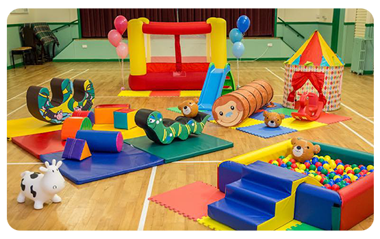 Small jumping castle and a variety of soft toys on a wooden floor