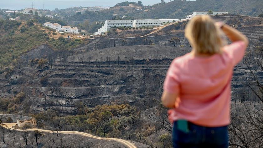 Una vecina observa la sierra calcinada por el incendio.