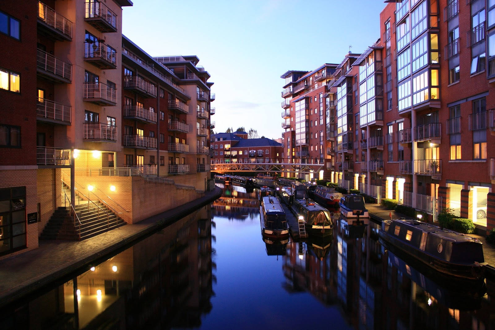 birmingham river during sunset. parked boats surrounded by red brick buildings with lights on, no people are seen. beautiful sunset in united kingdom