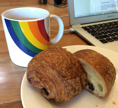Cup of coffee next to a plated croissant.