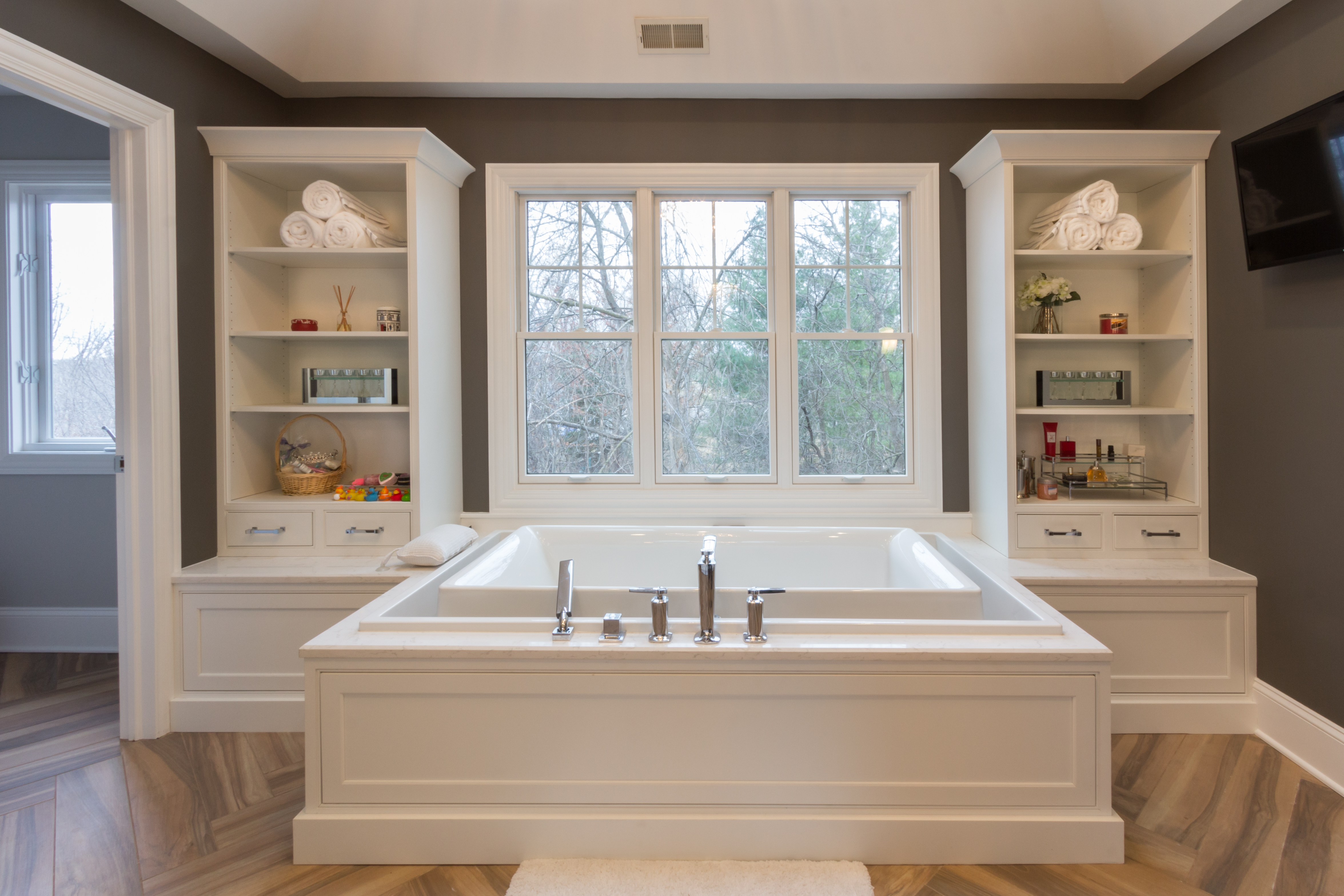 Large overflow tub under a picture window with built in shelving units on either side.