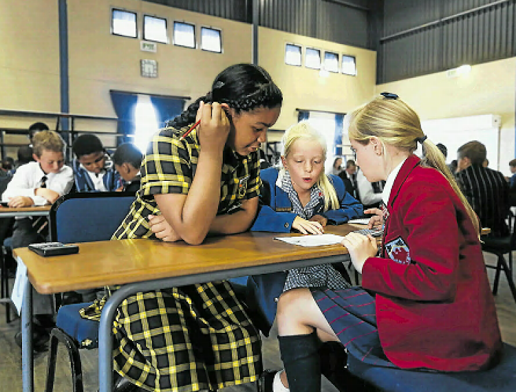 From left, Kelly-Anne Bherends, 10, Emma de Lange, 10, and Catherine Ludge, 10, work together to solve maths word problems at the annual MerriMathsMix at Merrifield School. The event emphasises camaraderie over competition and encourages pupils from different schools to work together.