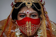 Sarayna Biswas, 6, wearing a face mask and dressed as Kumari wearing gold, takes part in a ritual during the Durga Puja festival celebrations at a pandal, or a temporary platform, amidst the outbreak of the coronavirus disease (Covid-19), in Kolkata, India, October 24, 2020.