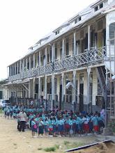 Photo: Schoolkinderen voor hun school, achter het bisdom