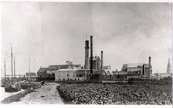 Photo: 1890 Gezien langs het onverharde jaagpad vanuit het noord-westen met rechts de Grote Kerk en links schepen die de suikerbieten aanleverden.