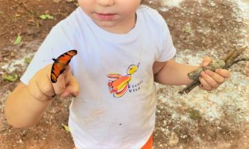 A imagem mostra uma criança com uma borboleta cor de laranja pousada no seu dedo.