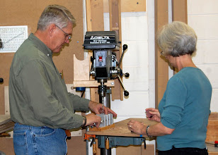 Photo: Bert Bleckwenn sets up the jig to hold the pen blanks as Mary Beardsley prepares to drill blanks.