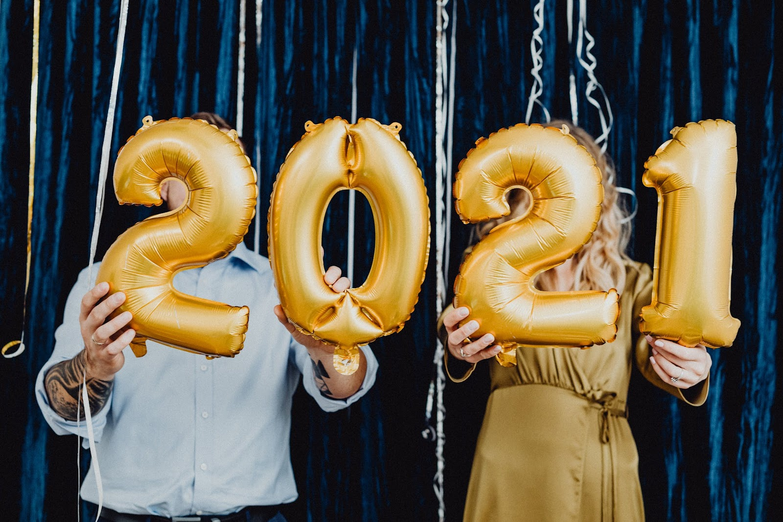 Two People Holding 2021 Golden Balloons