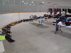 Photo: TONS of shoes donated .. all lined up from North entrance all the way around past the end of hanging dresses half way down the arena ..