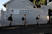 Pupils queue outside Clifton College in Durban as they wait to be disinfected.