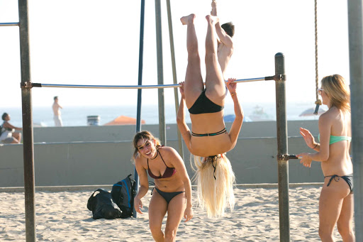 Young women goof off on the pullup bars on Muscle Beach in Venice, Calif.