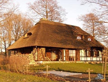 Dom z muru pruskiego z werandą i pokryciem trzcinowym jesienną porą