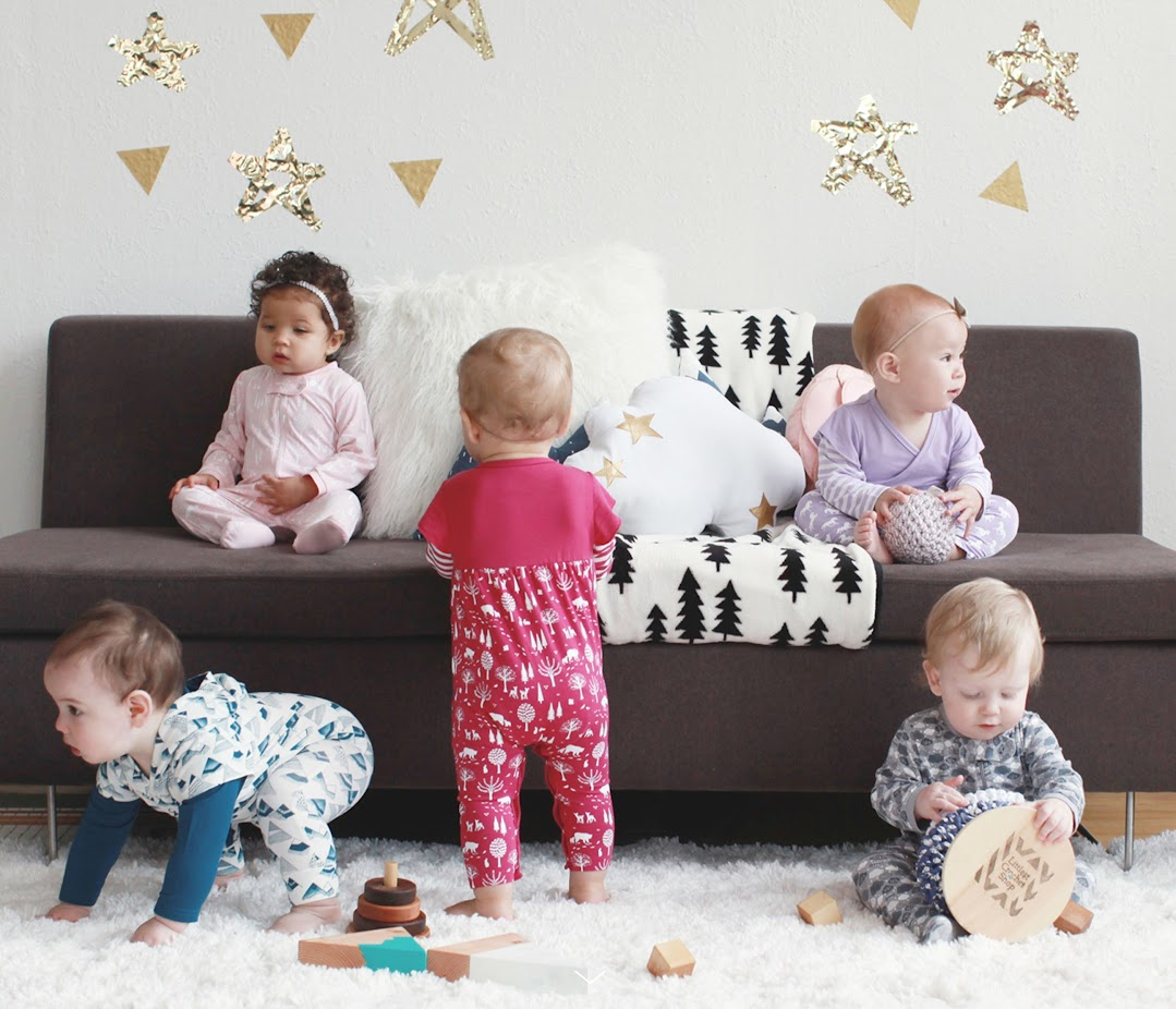 Five babies playing on & near a couch