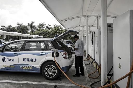 Filling up: A driver waits while a BYD electric taxi recharges at a charging station in Shenzhen. Picture: BLOOMBERG