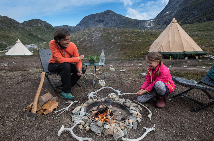 Greenlandic host Anika Krogh (left) roasting food on a fire.