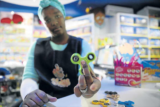 SALES ROCKET: An employee at Slater's Toy Magic in Berea holds up one of the latest toy sensations to hit the market, the fidget spinner Picture: SIBONGILE NGALWA