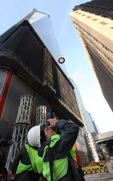 Photo: NEW YORK, NY - DECEMBER 12:  A photographer takes pictures as the first piece of the spire is hoisted atop One World Trade Center on December 12, 2012 in New York City.  The first of 18 sections of spire was hoisted atop the 104-story building by crane this morning.  (Photo by Mario Tama/Getty Images)