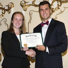 Photo: Awards Committee Chair Garrett Joyal presents Michigan Gamma President Kelsey Hockstadwith the R.C. Matthews Most Outstanding Chapter Award.