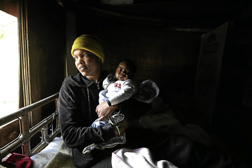 Alicia Koopman with her baby, Jordan, inside her home near Edenvale Hospital. The area is a hotspot for illegal settlement.