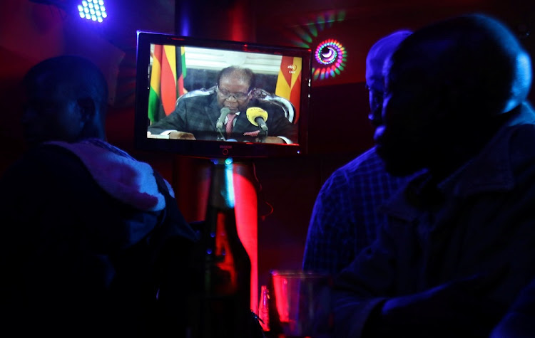 People watch as Zimbabwean President Robert Mugabe addresses the nation on television, in Harare, Zimbabwe, November 19, 2017. Picture: REUTERS