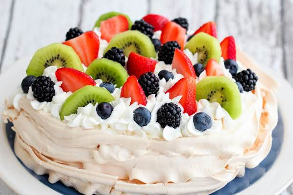 Australian Pavlova On A Cake Stand With Fresh Berries And Whipped Cream.